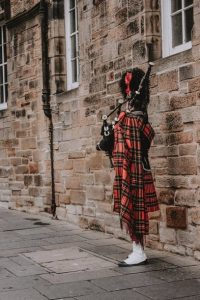 person playing the bagpipe and wearing a kilt