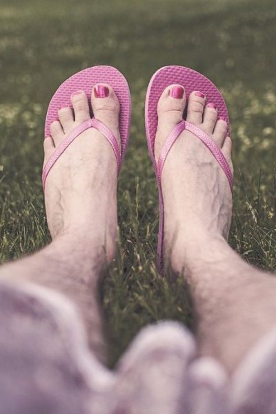 hairy legs wearing flip flops and pink nail polish